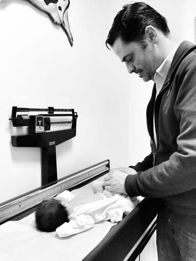 black and white iphone photo of newborn on weighing table with dad