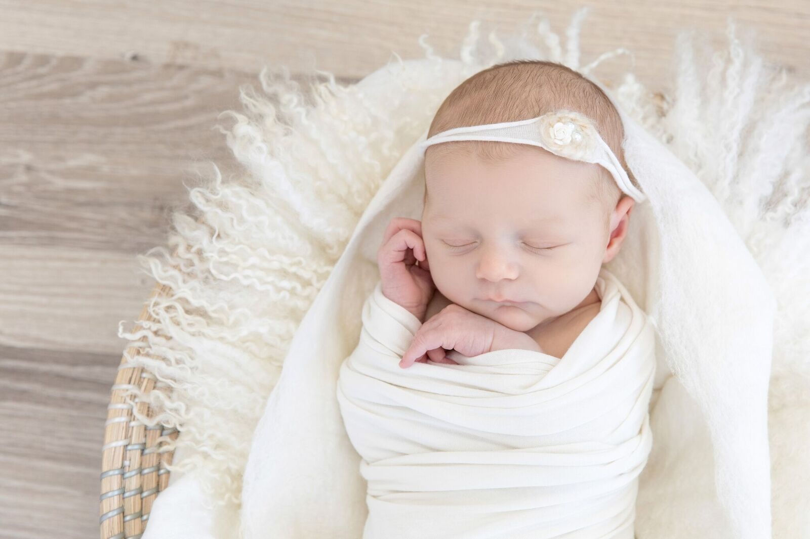 newborn girl wrapped in white blankets