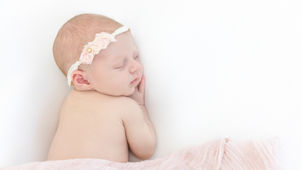 Image of newborn in pink wrap with headband during newborn photography shoot jane goodrich photography studio in larchmont, NY
