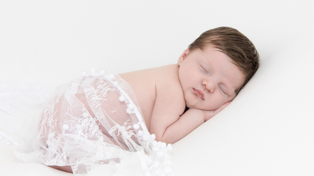 Image of newborn in white lace wrap during newborn photography shoot jane goodrich photography studio in larchmont, NY