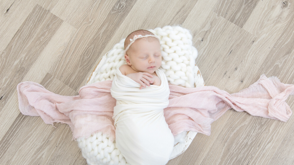 Image of newborn in white wrap with pink accent during newborn photography shoot jane goodrich photography studio in larchmont, NY