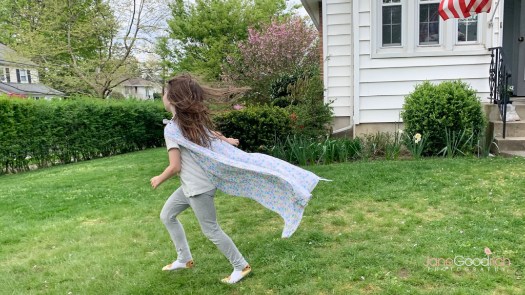 girl running in yard with cape Jane Goodrich Photography Larchmont, NY