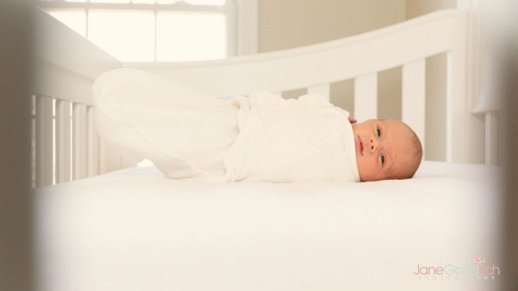 newborn in crib in white swaddle