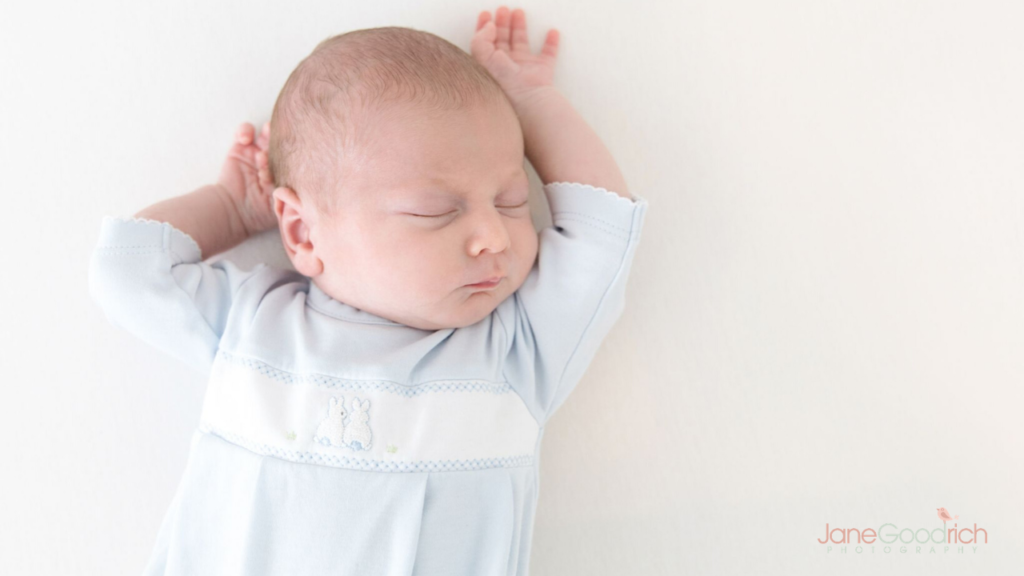 sleeping newborn in crib in light blue nightgown