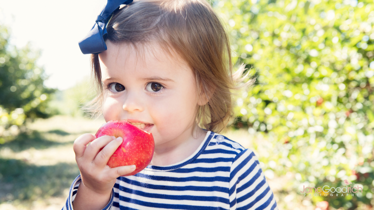 little girl eating apple how to photograph your kids digital course with Jane Goodrich